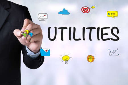 rent index: UTILITIES and Businessman drawing Landing Page on board Stock Photo