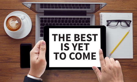 anticipated: THE BEST IS YET TO COME, on the tablet pc screen held by businessman hands - online, top view Stock Photo