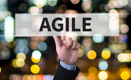 agile: Agile Agility Nimble Quick Fast Concept Business man with hand pressing a button on blurred abstract background