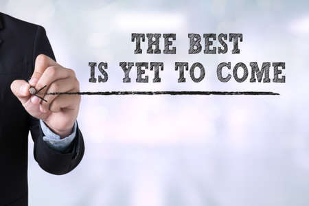 forthcoming: THE BEST IS YET TO COME Businessman drawing Landing Page on blurred abstract background