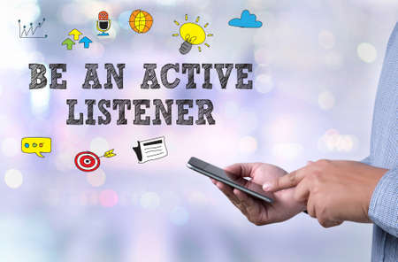 listener: BE AN ACTIVE LISTENER person holding a smartphone on blurred cityscape background Stock Photo