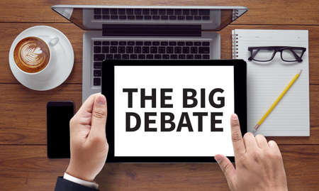 standpoint: THE BIG DEBATE on the tablet pc screen held by businessman hands, top view
