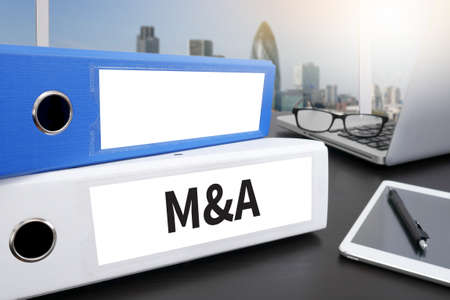 purchases: M&A (MERGERS AND ACQUISITIONS) Office folder on Desktop on table with Office Supplies.