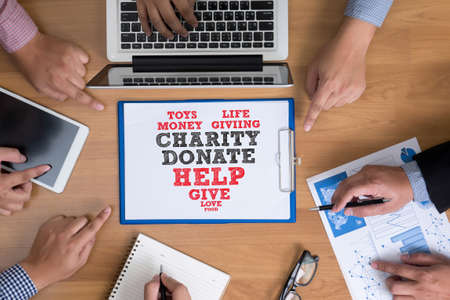 provide: CHARITY DONATE Give Concept Business team hands at work with financial reports and a laptop, top view