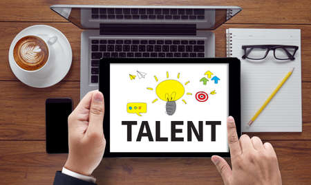 gifted: TALENT (Gifted Skills Abilities Capability Expertise), on the tablet pc screen held by businessman hands - online, top view Stock Photo