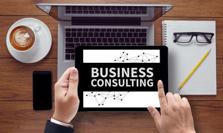 consult: BUSINESS CONSULTING CONCEPT , on the tablet pc screen held by businessman hands - online, top view