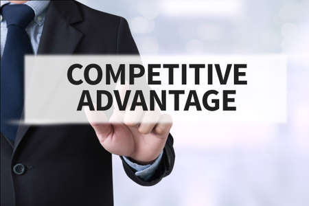 strategic advantage: COMPETITIVE ADVANTAGE Businessman hands touching on virtual screen and blurred city background