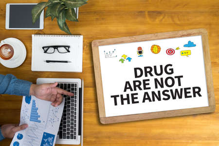 religious habit: DRUG ARE NOT THE ANSWER Businessman working at office desk and using computer and objects, coffee, top view,