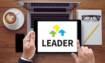 authoritarian: LEADER ( Leader Leadership Manager Management Director ), on the tablet pc screen held by businessman hands - online, top view
