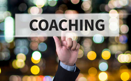 tutor: COACHING (Guide Instructor Leader Manager Tutor ) Business man with hand pressing a button on blurred abstract background Stock Photo