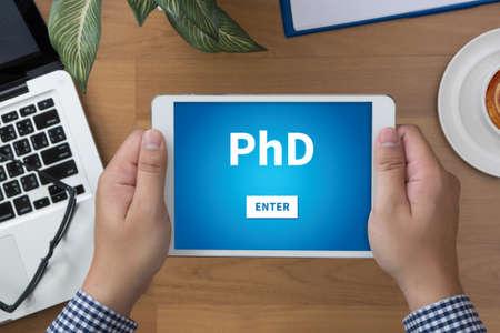 PhD Doctor en Filosofía Grado de Educación de la graduación de la tableta hombre de la mano y la taza de café Foto de archivo