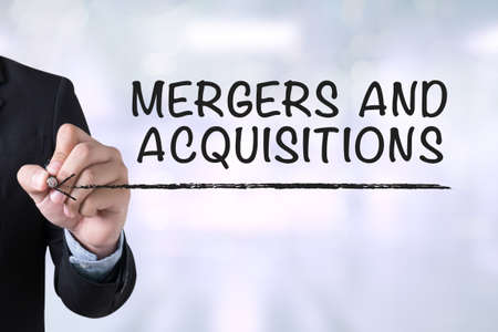 acquisitions: MERGERS AND ACQUISITIONS   M&A  Businessman drawing Landing Page on blurred abstract background Stock Photo