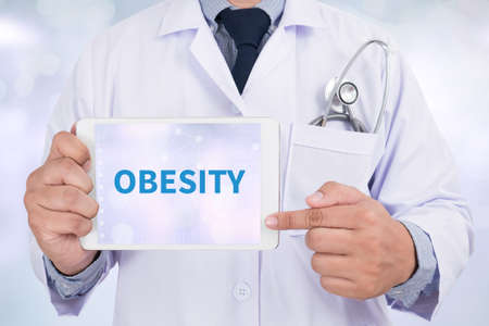 obesidad infantil: OBESIDAD Doctor que sostiene la tableta digital