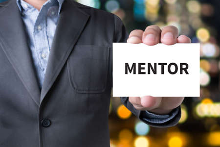 mentors: MENTOR CONCEPT Businessman message on the card shown on blurred city background, holding empty white card Stock Photo