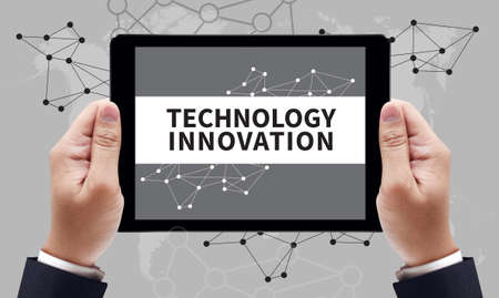 technological evolution: TECHNOLOGY INNOVATION CONCEPT on the tablet pc screen by businessman hands, top view