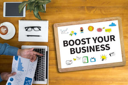 wealthy lifestyle: BOOST YOUR BUSINESS Businessman working at office desk and using computer and objects, coffee, top view,