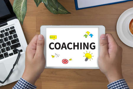 tutor: COACHING (Guide Instructor Leader Manager Tutor ) man hand Tablet and coffee cup Stock Photo