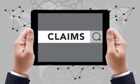 CLAIMS CONCEPT on the tablet pc screen by businessman hands, top view