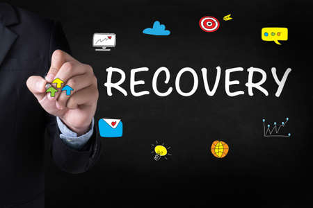 data recovery: RECOVERY (Recovery Backup Restoration Data) Businessman drawing Landing Page on blurred abstract background