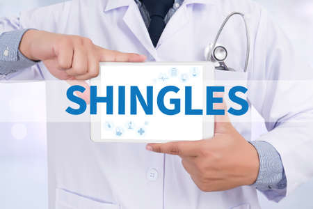 shingles: SHINGLES Doctor holding  digital tablet