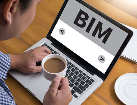developement: BIM Businessman at work. Close-up top view of man working on laptop while sitting at the wooden desk , coffee
