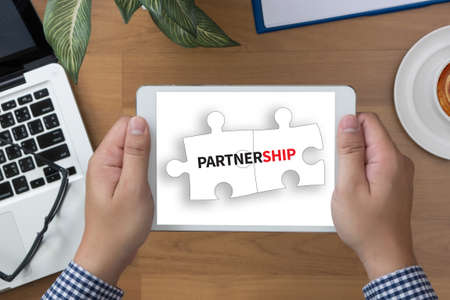 synergism: PARTNERSHIP man hand Tablet and coffee cup Stock Photo