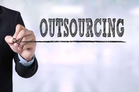 offshoring: OUTSOURCING Businessman drawing Landing Page on blurred abstract background