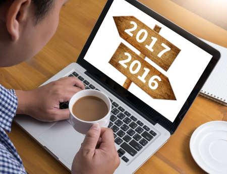 next horizon: 2016 2017 Businessman at work. Close-up top view of man working on laptop while sitting at the wooden desk , coffee