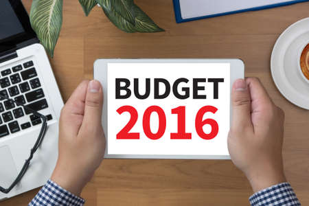 marginal returns: BUDGET 2016 man hand Tablet and coffee cup