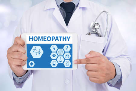 homeopathy: HOMEOPATHY Doctor holding  digital tablet Stock Photo