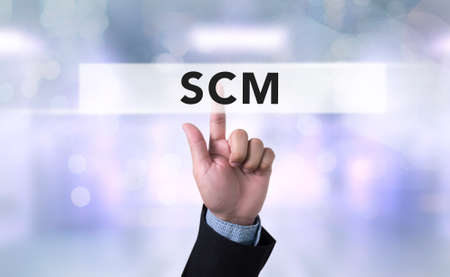 scm: SCM Supply Chain Management concept Business man with hand pressing a button on blurred abstract background