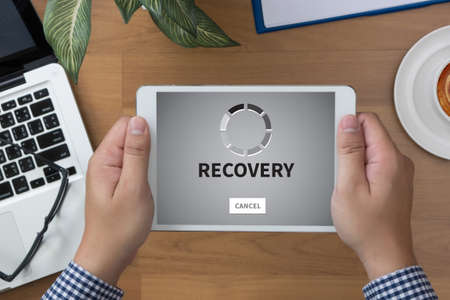 data recovery: RECOVERY (Recovery Backup Restoration Data) man hand Tablet and coffee cup Stock Photo