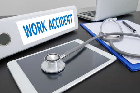 death head holding: WORK ACCIDENT folder on Desktop on table. Stock Photo