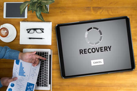 data recovery: RECOVERY (Recovery Backup Restoration Data) Businessman working at office desk and using computer and objects, coffee, top view,
