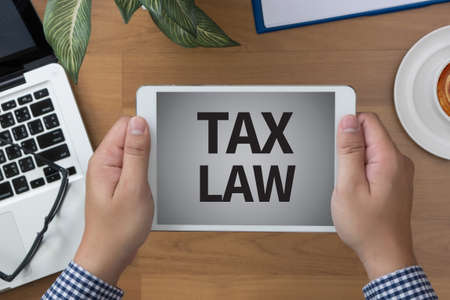 tax law: TAX LAW                man hand Tablet and coffee cup