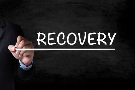 data recovery: RECOVERY (Recovery Backup Restoration Data) and Businessman drawing  Page on blackboard Stock Photo