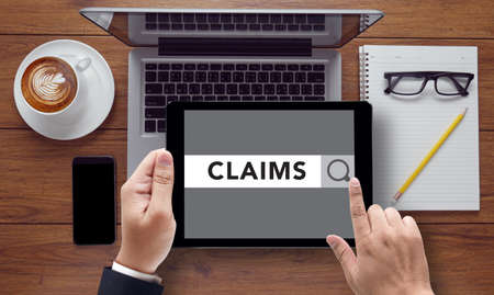 claims: CLAIMS CONCEPT , on the tablet pc screen held by businessman hands - online, top view