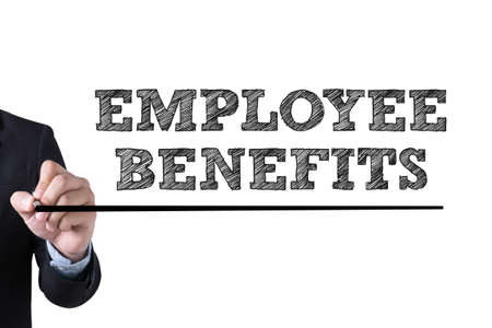 additional compensation: EMPLOYEE BENEFITS Businessman hand writing with black marker on white background Stock Photo