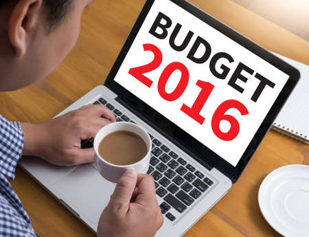 BUDGET 2016 Businessman at work. Close-up top view of man working on laptop while sitting at the wooden desk , coffee
