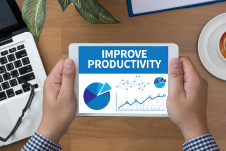throughput: IMPROVE PRODUCTIVITY man hand Tablet and coffee cup Stock Photo