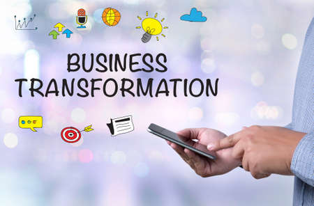 modernize: BUSINESS TRANSFORMATION person holding a smartphone on blurred cityscape background