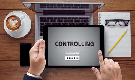 assert: CONTROLLING, on the tablet pc screen held by businessman hands - online, top view Stock Photo