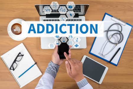 physiological: ADDICTION Doctor working at office desk and using a mobile touch screen phone, computer and medical equipment all around, top view, coffee
