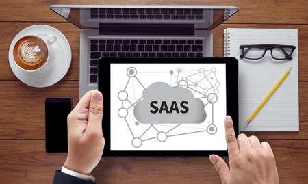 saas fee: SAAS, on the tablet pc screen held by businessman hands - online, top view