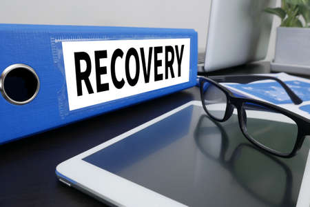 data recovery: RECOVERY (Recovery Backup Restoration Data) Office folder on Desktop on table with Office Supplies. Stock Photo