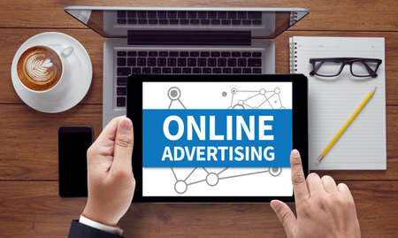 interstitial: ONLINE ADVERTISING, on the tablet pc screen held by businessman hands - online, top view