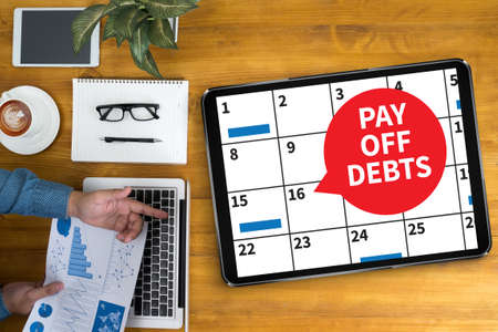 pay off: PAY OFF DEBTS Loan Money Bankruptcy Bill  Businessman working at office desk and using computer and objects, coffee, top view,