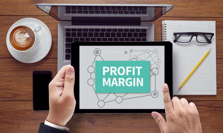 margen: PROFIT MARGIN , on the tablet pc screen held by businessman hands - online, top view Foto de archivo