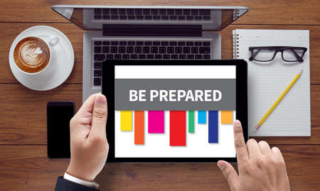 be prepared: BE PREPARED concept, on the tablet pc screen held by businessman hands - online, top view Stock Photo