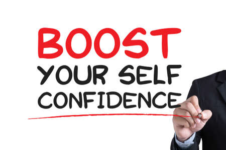 BOOST YOUR SELF CONFIDENCE Businessman hand writing with black marker on white background